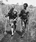 Wounded Australian soldier led by a Papuan orderly at Buna
